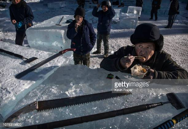 Chinese worker eats his lunch as his cutting tools rest on a large ice block while building an ice sculpture in preparation for the Harbin Ice and...