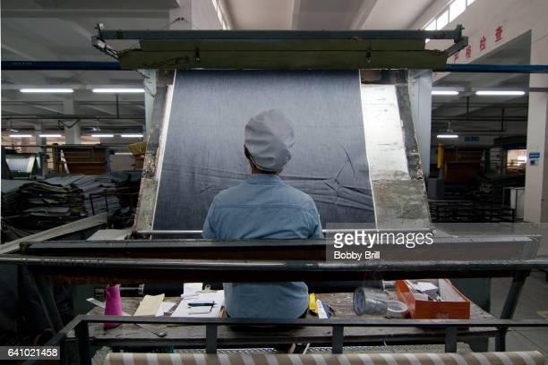 chinese worker examines denim fabric in a factory - denim foto e immagini stock