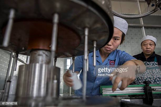 Chinese worker fills bottles with locally made wine called baijiu at the Guizhou Huaizhuang Liquor Group on September 22 2016 in MaotaiGuizhou...