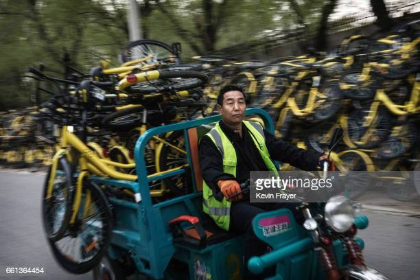 Chinese worker from the bike share company Ofo Inc transports bicycles collected from the streets to a repair depot for the company on March 30 2017...