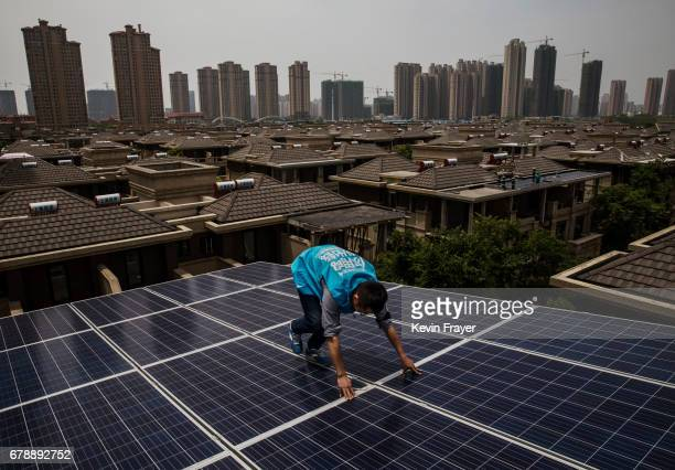Chinese worker from Wuhan Guangsheng Photovoltaic Company walks carefully while installing a solar panel project on the roof of a building on April...