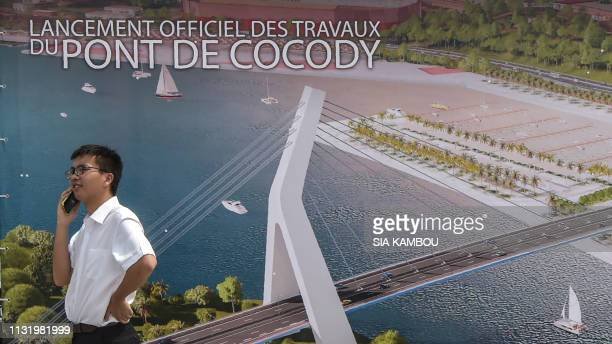 A Chinese worker gives a phone call in front of a poster on March 22 2019 depicting a drawing of the 5th CocodyPlateau bridge in Abidjan during the...