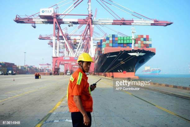 A Chinese worker looks on as a cargo ship is loaded at a port in Qingdao eastern China's Shandong province on July 13 2017 China's exports rose a...