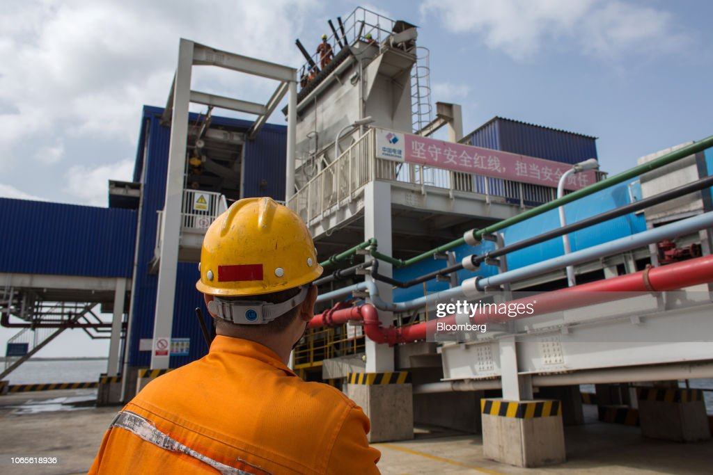 A Chinese worker looks up at colleagues on a loading jetty