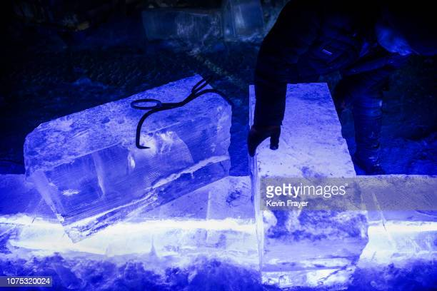 Chinese worker moves a piece of ice while working on ice sculptures in preparation for the Harbin Ice and Snow Festival on December 19 2018 in Harbin...