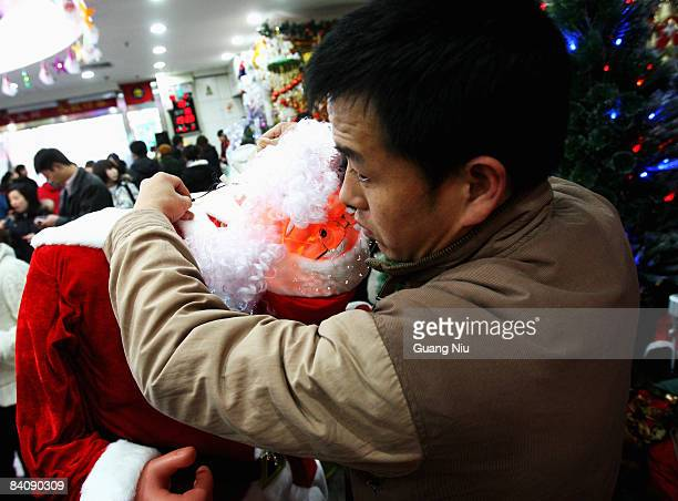 Chinese worker of a Christmas decorations store installs models of Santa Claus at a market on December 19 2008 in Beijing China A large number of...