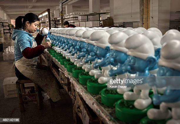 Chinese worker paints unfinished licensed ceramic 'Smurfs' at the Shunmei Group ceramics factory during a tour on December 7 2014 in DehuaFujian...