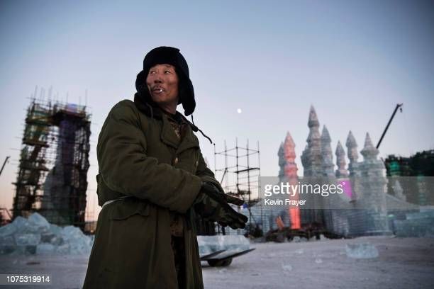 Chinese worker pauses while offloading large ice blocks cut from the nearby Songhua River to be used for ice sculptures in preparation for the Harbin...