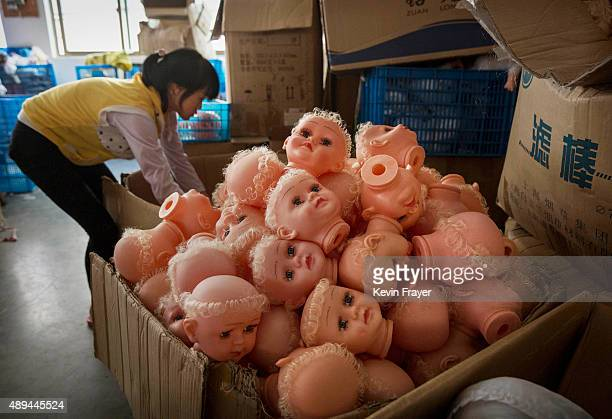 Chinese worker piles doll heads at a toy factory on September 17 2015 in Xietang Zhejiang ProvinceChina Many of the toy factories in the area have...