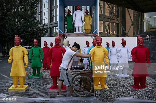 Chinese worker places stones in front of statues replicating China's famous Terracotta Warriors at an exhibtion on September 3 2014 in Beijing China...