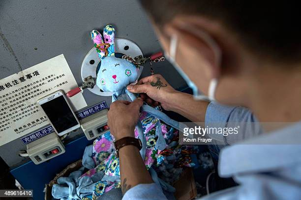 Chinese worker prepares a stuffed toy at a factory on September 17 2015 in Zhejiang China Many of the toy factories in the area have seen a sharp...