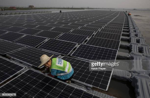 Chinese worker prepares connects panels that are part of a large floating solar farm project under construction by the Sungrow Power Supply Company...