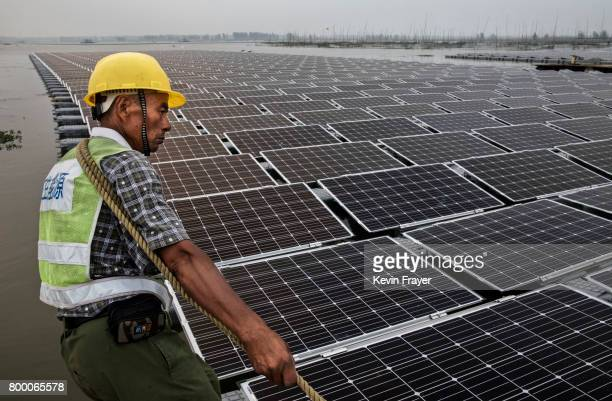 Chinese worker pulls floating panels that are part of a large floating solar farm project under construction by the Sungrow Power Supply Company on a...