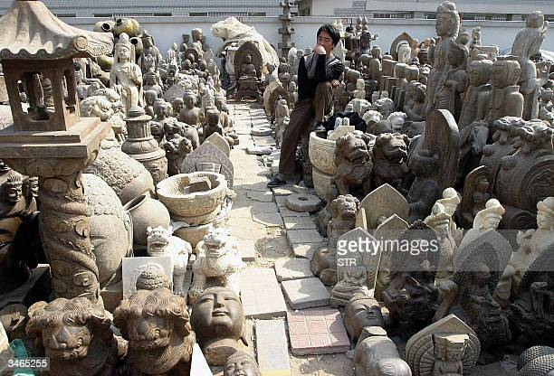 Chinese worker rests in between various replicas of antique statues at an antique market in Beijing 25 April 2004 which also offers real antique...