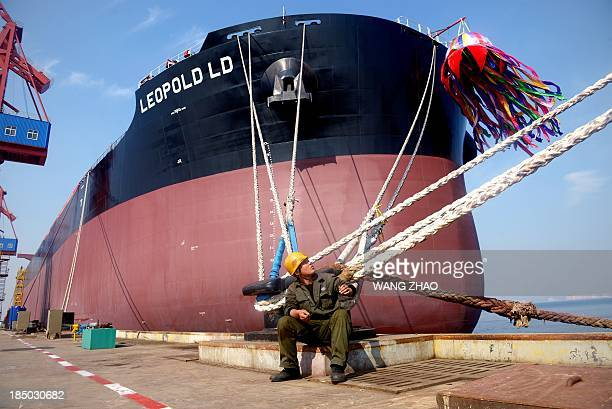 A Chinese worker rests in front of a bulk carrier of during a naming ceremony at a shipyard in Tianjin on October 17 2013 Three bulk carriers ordered...