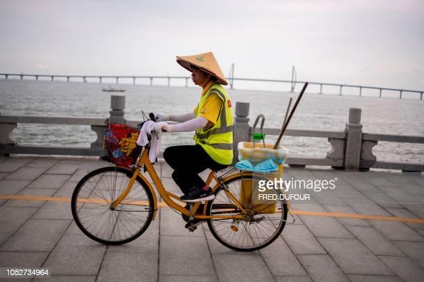 A Chinese worker rides his bike near Hong KongZhuhaiMacau Bridge in Zhuhai on October 22 on the eve of its opening ceremony The world's longest sea...