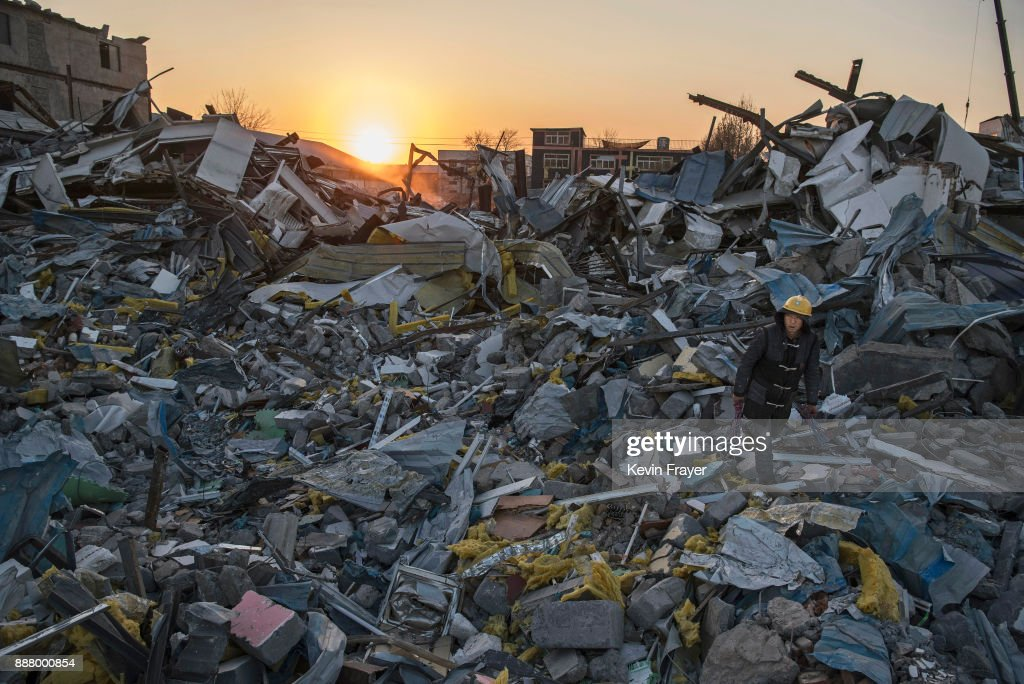 A Chinese worker salvages items from buildings demolished by authorities in an area that used to have migrant housing and factories on December 6, 2017 in the Daxing District of Beijing, China.Thousands of migrant workers have been forcibly evicted in recent weeks in a sweeping government safety campaign following a deadly fire at a housing settlement. Many migrants, who came to Beijing from poor rural areas to find employment, say they were given little notice to leave and cannot afford to move somewhere else. The government's plan to demolish the buildings was actually announced in a 2015 strategy to reduce and cap the capital's population, but the mass evictions were accelerated after the fire and have stirred public backlash. The migrant population typically work in jobs such as construction, sanitation, and deliveries that have effectively built Beijing and keep it running. Some companies announced assistance and temporary housing for employees who have been affected, but many migrants say they have little choice but to move back to their hometowns.