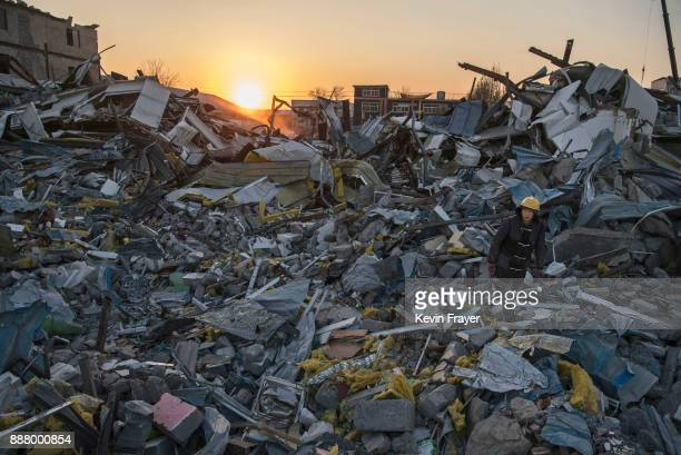 Chinese worker salvages items from buildings demolished by authorities in an area that used to have migrant housing and factories on December 6 2017...