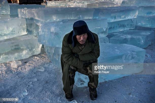 Chinese worker sits in blocks of ice as he takes a break while working on ice sculptures in preparation for the Harbin Ice and Snow Festival on...