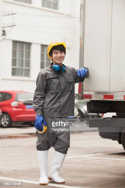 chinese worker standing outdoors - ear protection stock pictures, royalty-free photos & images