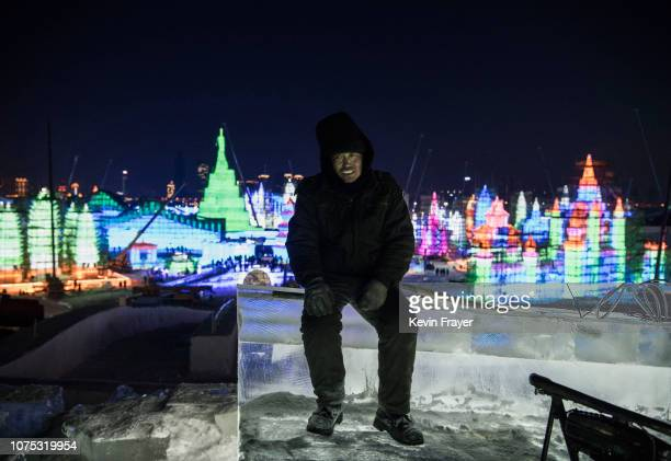 Chinese worker takes a break as he rests on ice sculptures he and others built in preparation for the Harbin Ice and Snow Festival on December 19...