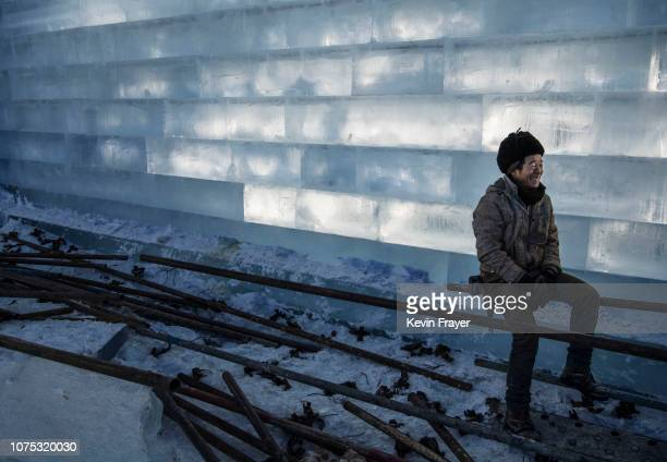 Chinese worker takes a break while working on ice sculptures in preparation for the Harbin Ice and Snow Festival on December 19 2018 in Harbin China...