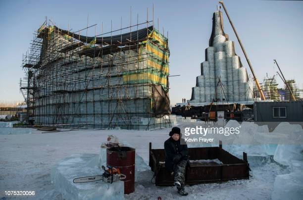 Chinese worker takes a break while working on ice sculptures in preparation for the Harbin Ice and Snow Festival on December 19 2018 in Harbin...