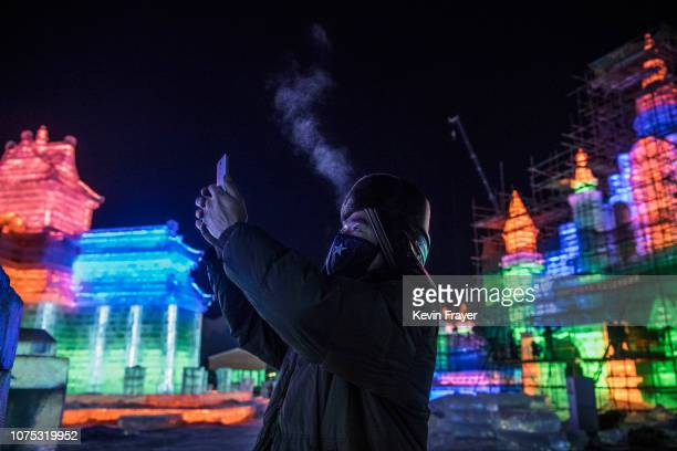 Chinese worker takes a picture with his phone of ice sculptures he and others built in preparation for the Harbin Ice and Snow Festival on December...