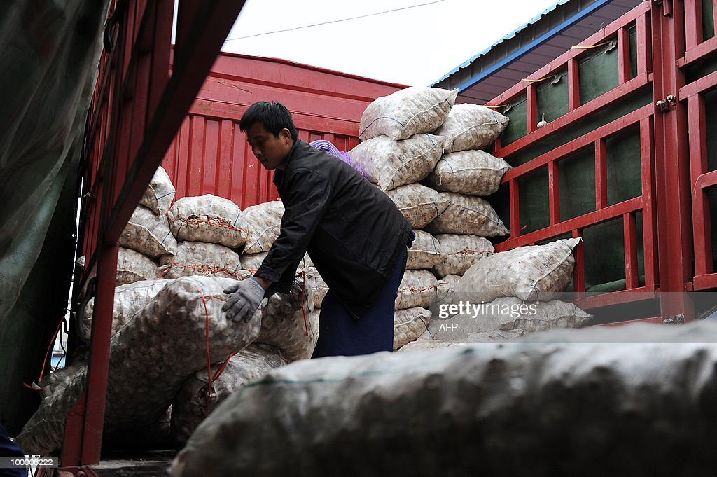 A Chinese worker unloads bags of garlic at a market in Hefei, central China's Anhui province on May 19, 2010. China said that consumer prices and bank lending accelerated in April, fuelling fears the economy may overheat and building pressure on Beijing to hike interest rates and let its currency rise. CHINA