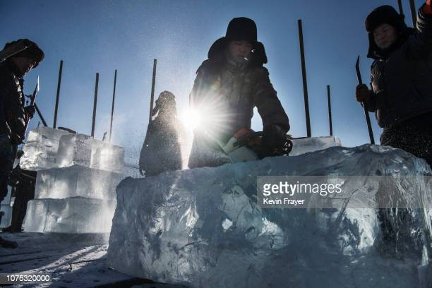 Chinese worker uses a chain saw to cut a large cube of ice from the frozen Songhua River while working on ice sculptures in preparation for the...