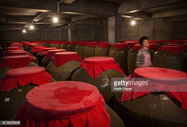 Chinese worker walks passed vats of locally made wine called baijiu at a distillery on the Chishui RIver on September 23 2016 in MaotaiGuizhou...