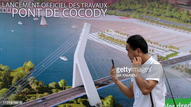A Chinese worker walks past a poster on March 22 2019 depicting a drawing of the 5th CocodyPlateau bridge in Abidjan during the official launch of...