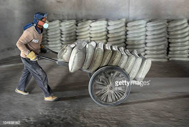 A Chinese worker wears a mask as he delivers bags of cement at a factory in Hefei east China's Anhui province on October 6 2010 China in 2009...