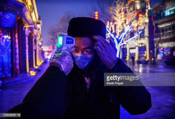 Chinese worker wears a protective mask as he has his temperature checked in a nearly empty and shuttered commercial street on February 12, 2020 in...