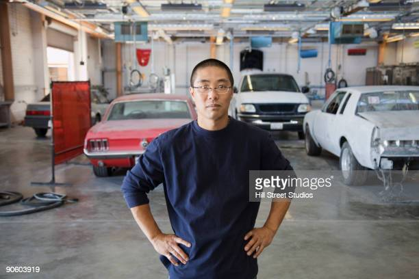 Chinese worker with hands on hips in auto body shop