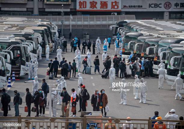 Chinese workers and health officials wear protective white suits as travellers from Wuhan gather to take buses as they are processed and taken to do...
