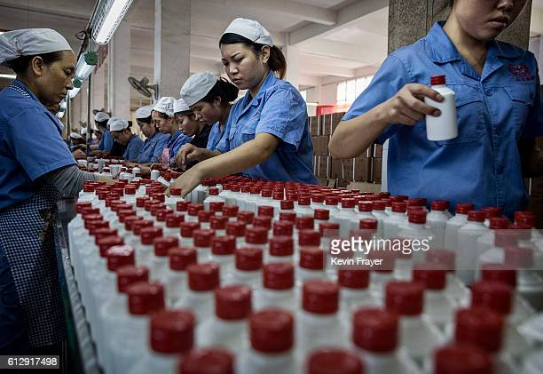 Chinese workers arrange bottles of quality locally made wine called baijiu at the Guizhou Huaizhuang Liquor Group on September 22 2016 in...