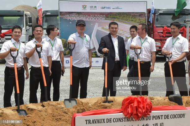 Chinese workers attend on March 22 2019 on March 22 2019 the official launch of the construction work of the 5th CocodyPlateau bridge in Abidjan...