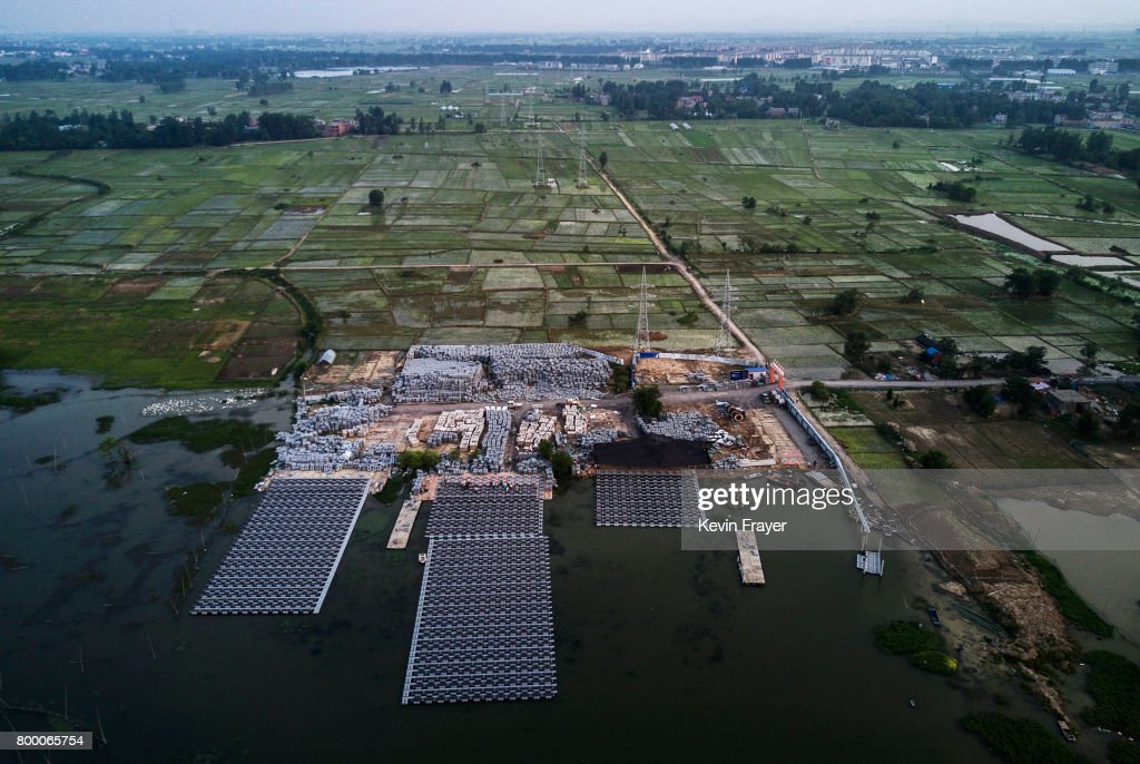 Chinese workers build sections of a large floating solar farm project under construction by the Sungrow Power Supply Company on a lake caused by a collapsed and flooded coal mine on June 13, 2017 in Huainan, Anhui province, China. The floating solar field, billed as the largest in the world, is built on a part of the collapsed Panji No.1 coal mine that flooded over a decade ago due to over-mining, a common occurence in deep-well mining in China's coal heartland. When finished, the solar farm will be made up of more than 166,000 solar panels which convert sunlight to energy, and the site could potentially produce enough energy to power a city in Anhui province, regarded as one of the country's coal centers. Local officials say they are planning more projects like it, marking a significant shift in an area where long-term intensive coal mining has led to large areas of subsidence and environmental degradation. However, the energy transition has its challenges, primarily competitive pressure from the deeply-established coal industry that has at times led to delays in connecting solar projects to the state grid. China's government says it will spend over US $360 billion on clean energy projects by 2020 to help shift the country away from a dependence on fossil fuels, and earlier this year, Beijing canceled plans to build more than 100 coal-fired plants in a bid to ease overcapacity and limit carbon emissions. Already, China is the leading producer of solar energy, but it also remains the planet's top emitter of greenhouse gases and accounts for about half of the world's total coal consumption.