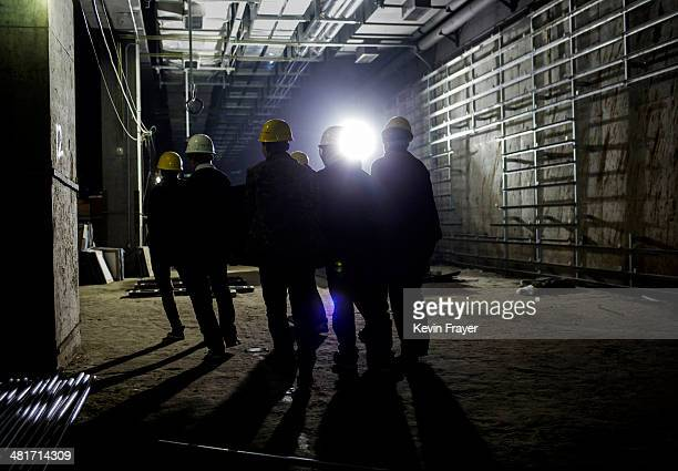 Chinese workers carry equipment while working on a a new subway line on March 29 2014 in Beijing China The new line will be the 18th in the Beijing...