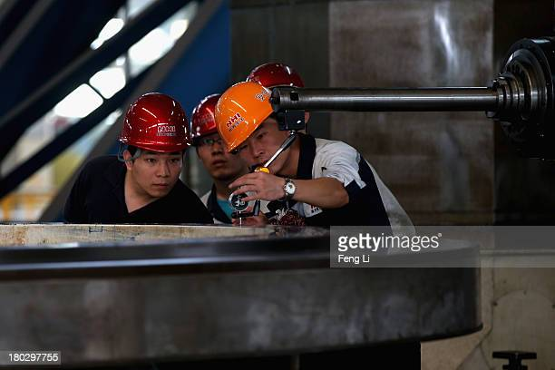 Chinese workers check the mining engineering equipment at Northern Heavy Industries Group Co Ltd on September 9 2013 in Shenyang of Liaoning Province...