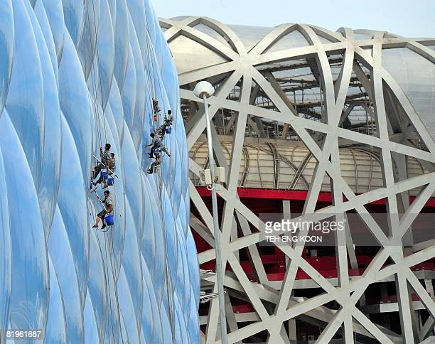 Chinese workers clean the exterior of the National Aquatics Center better known as the Water Cube near the National Stadium also known as the Bird's...