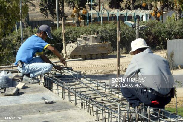 Chinese workers construct a new floor on top the roof of a house in the settlement of Kfar Darom, 24 October 2004, in the southern Gaza strip. The...