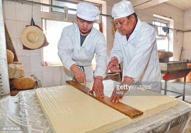 Chinese workers cut tofu into pieces before making white fermented tofu on May 3 2018 in Qinhuangdao Hebei Province of China