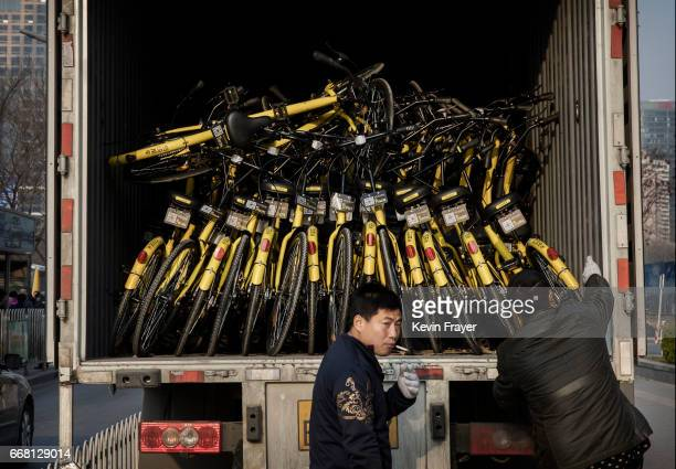 Chinese workers from the ride share bicycle company Ofo prepare to unload new bikes from a truck during rush hour on March 28 2017 in Beijing China...