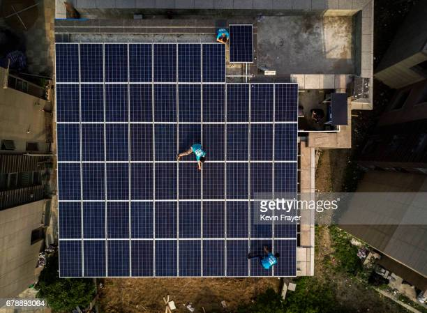 Chinese workers from Wuhan Guangsheng Photovoltaic Company walk on a solar panel project on the roof of a building on April 27 2017 in Wuhan China As...