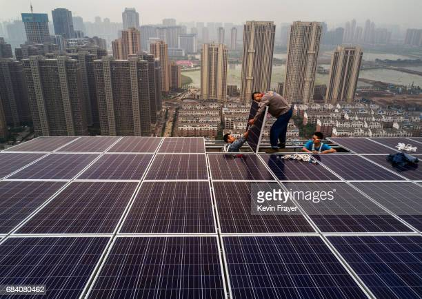 Chinese workers from Wuhan Guangsheng Photovoltaic Company work on a solar panel project on the roof of a 47 story building in a new development on...