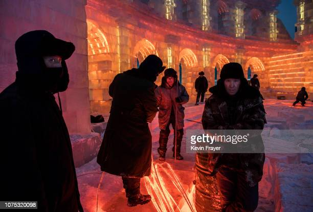 Chinese workers gather lights that will be placed inside ice sculptures in preparation for the Harbin Ice and Snow Festival on December 22 2018 in...