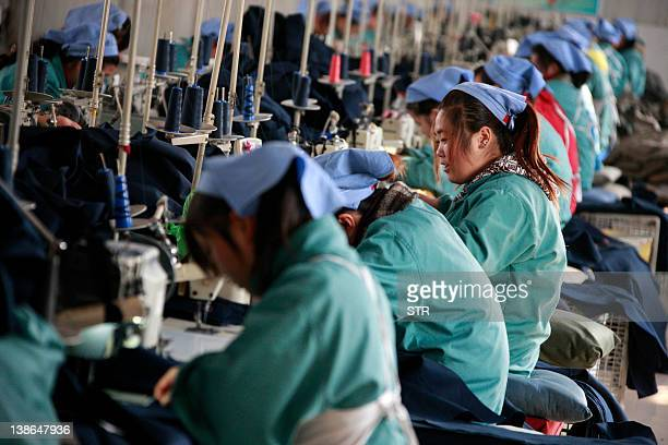 Chinese workers go about their chores at a textile factory in Huaibei, Anhui province in China on February 10, 2012. China's trade activity fell in...