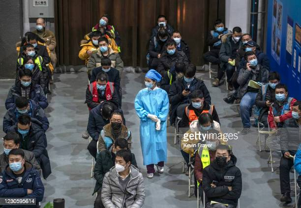 Chinese workers, including security guards, wait to receive a COVID-19 vaccine jab at a mass vaccination center for Chaoyang District on January 15,...